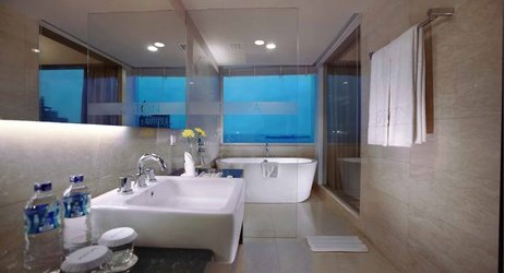 A nicely appointed bathroom with bathtub and complete amenities in and glass wall in makassar