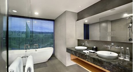 Modern bathroom with porcelain bath tub and sink completed with exclusive mountain view in Sentul area