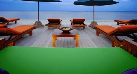 A beachfront sundeck with sunset view in a beautiful resort to stay when visit gili trawangan island lombok for holiday