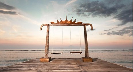 A beach swing to enjoy sunset in a beautiful resort to stay when visit gili trawangan island lombok for holiday