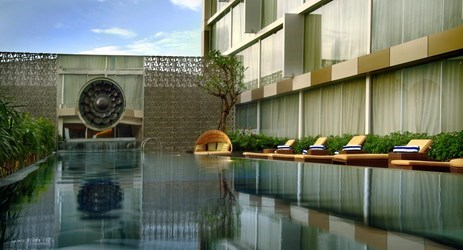 The inviting outdoor swimming pool surrounded by open-air deck and sun loungers from which to enjoy the relaxing atmosphere of Yogyakarta sky