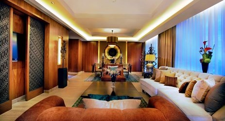 The grandeur of hotel living room at Grand Aston Yogyakarta exposing relaxing sofa and cushion with magnificent view of mount Merapi