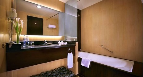 A nicely appointed bathroom with bathtub and shower in a modern stylish classy hotel in kuta bali