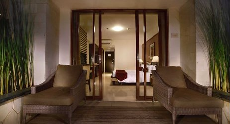 Spacious private balcony overviewing the pool or garden in modern luxurious hotel in kuta bal