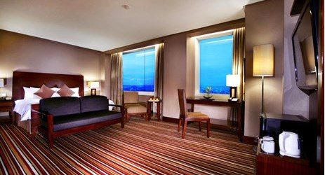 A clean, comfortable and spacious room with carpet, couch, working desk, and king-size bed a perfect place to sleep or relax while have a business or holiday in Samarinda.