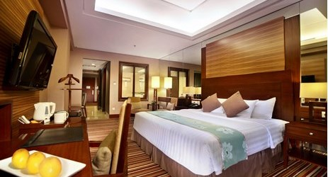 A clean, comfortable and spacious room with carpet, living room area, working desk, and king-size bed a perfect place to sleep or relax while have a business or holiday in Samarinda.